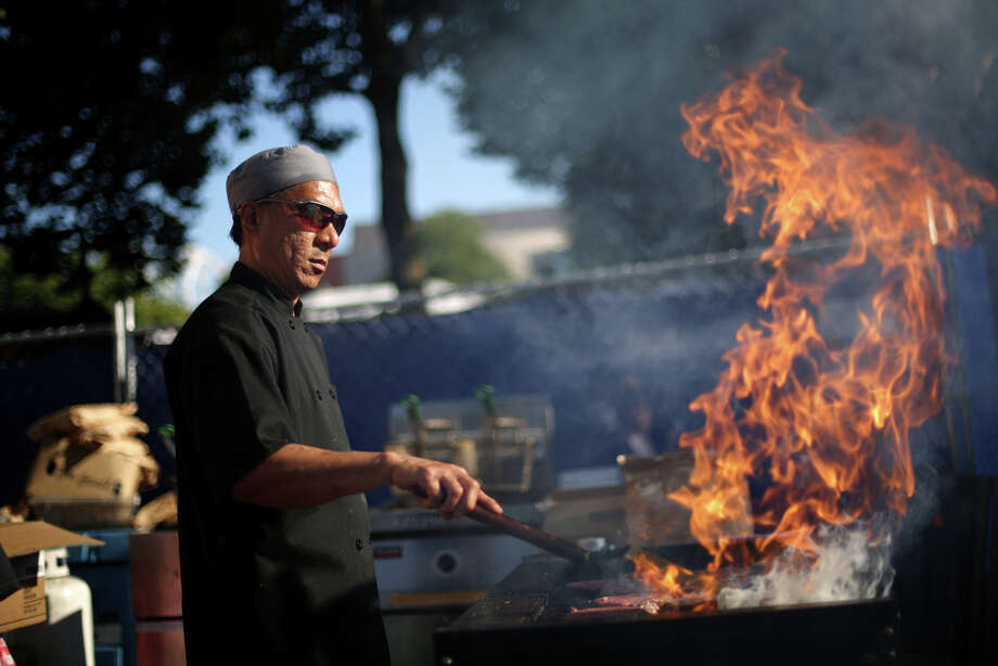 Dominic Cordova of Classic Catering fires up a grill during the first day of the annual Bite of Seattle on Friday, July 19, 2013 at the Seattle Center. The event features food from dozens of local restaurants and food vendors. The Bite of Seattle runs through Sunday evening. Photo: JOSHUA TRUJILLO, SEATTLEPI.COM / SEATTLEPI.COM