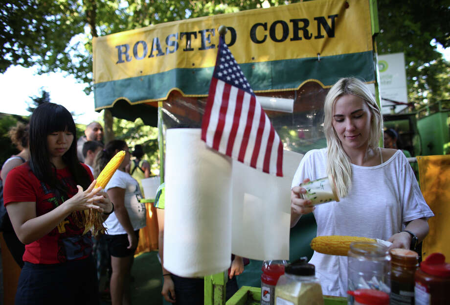 Kajsa Boline, right, adds salt to her roasted corn during the first day of the annual Bite of Seattle on Friday, July 19, 2013 at the Seattle Center. The event features food from dozens of local restaurants and food vendors. The Bite of Seattle runs through Sunday evening. Photo: JOSHUA TRUJILLO, SEATTLEPI.COM / SEATTLEPI.COM