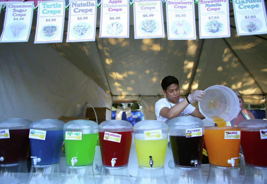 Emmanuel Rivera refills a juice dispenser during the first day of the annual Bite of Seattle on Friday, July 19, 2013 at the Seattle Center. The event features food from dozens of local restaurants and food vendors. The Bite of Seattle runs through Sunday evening. Photo: JOSHUA TRUJILLO, SEATTLEPI.COM / SEATTLEPI.COM