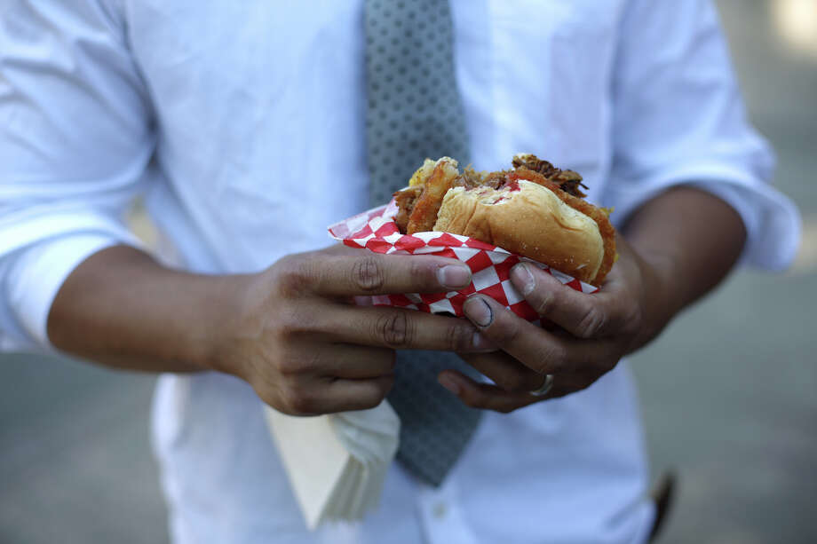 A man eats an adobo sandwich during the first day of the annual Bite of Seattle on Friday, July 19, 2013 at the Seattle Center. The event features food from dozens of local restaurants and food vendors. The Bite of Seattle runs through Sunday evening. Photo: JOSHUA TRUJILLO, SEATTLEPI.COM / SEATTLEPI.COM