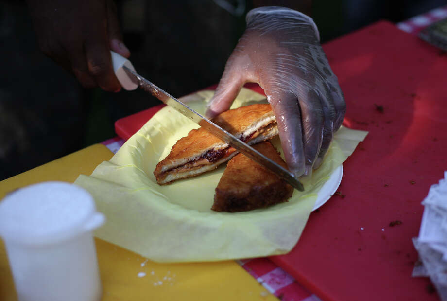 A fried PB&J is cut for a customer during the first day of the annual Bite of Seattle on Friday, July 19, 2013 at the Seattle Center. The event features food from dozens of local restaurants and food vendors. The Bite of Seattle runs through Sunday evening. Photo: JOSHUA TRUJILLO, SEATTLEPI.COM / SEATTLEPI.COM