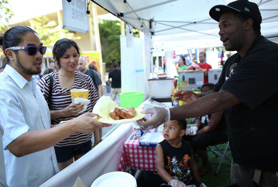 Elisha Walton, right, serves customers a deep-fried PB&J during the first day of the annual Bite of Seattle on Friday, July 19, 2013 at the Seattle Center. The event features food from dozens of local restaurants and food vendors. The Bite of Seattle runs through Sunday evening. Photo: JOSHUA TRUJILLO, SEATTLEPI.COM / SEATTLEPI.COM