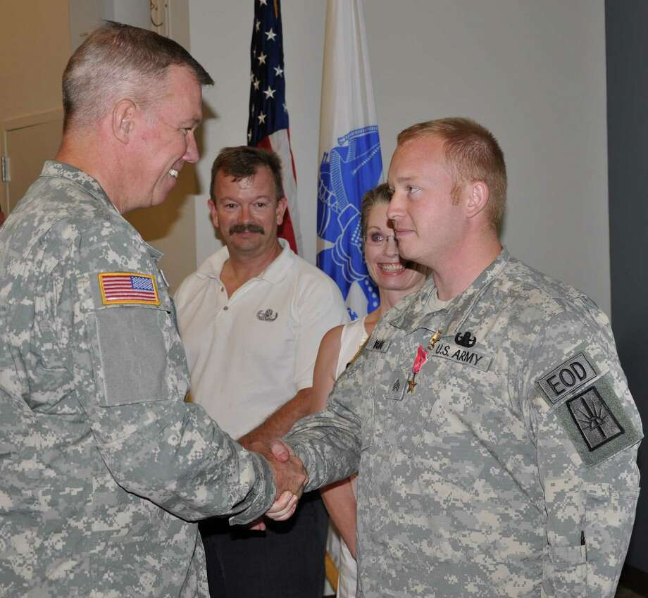 New York Army National Guard  Sgt. Joshua Young assigned to the 1108th Ordnance Company (Explosive Ordnance Disposal) is congratulated by Brig. Gen. Mike Swezey, Commander of the 53rd Troop Command, after receiving the  the Bronze Star Medal with V Device at the Scotia-Glenville Armed Forces Reserve Center in Glenville,  on Friday,  July 19th.  Young's parents Tim and Kim,  traveled from Fairport, N.Y. to participate in the ceremony with their son. Young was recognized for saving the life of a fellow Soldier in Afghanistan in March 2012.