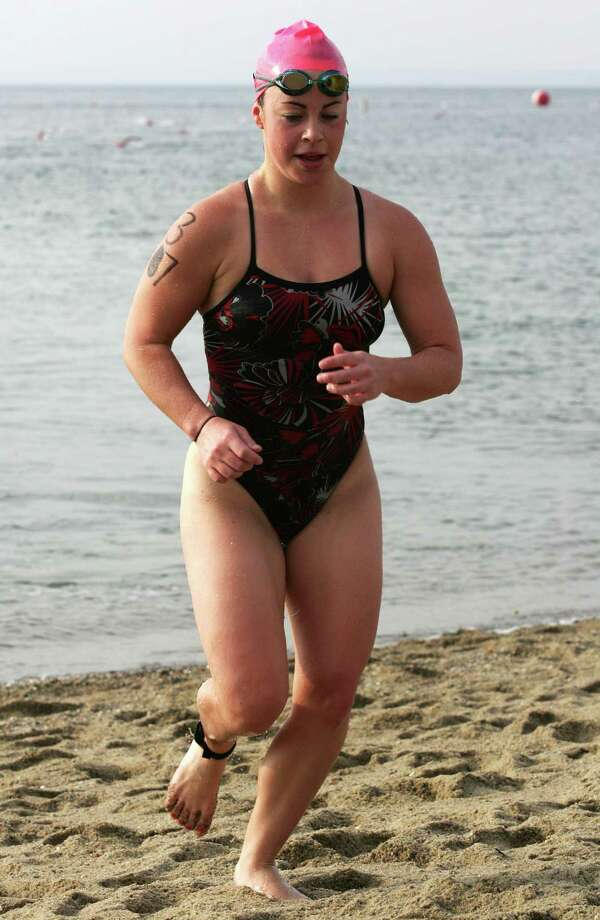 Colleen Moore, 21, from Ridgefield was the first woman out of the water, with a time of 16:59, at the 26th Annual Greenwich Point One Mile Swim Saturday, July 20, 2013. Photo: David Ames / Greenwich Time Freelance