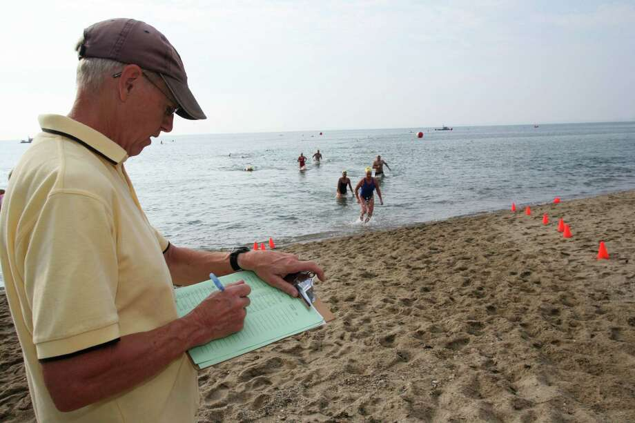 Bill Weinheimer records finishing times during this years 26th Annual Greenwich Point One Mile Swim Saturday, July 20, 3013. Photo: David Ames / Greenwich Time Freelance