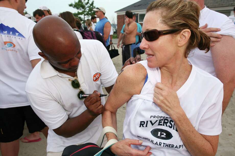 Bobbi Hanson, right, gets a number applied to her arm by Delano Copprue before the start of the 26th Annual Greenwich Point One Mile Swim Saturday, July 20, 2013. Photo: David Ames / Greenwich Time Freelance