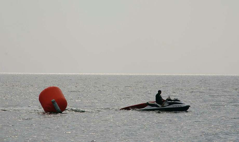 The tide carried away one buoy marker for the Point-to-Point race, but the police marine patrol was able to apprehend the getaway guidepost and reattach it to mark the race route.  WESTPORT NEWS, CT 7/20/13 Photo: Jarret Liotta / Westport News contributed