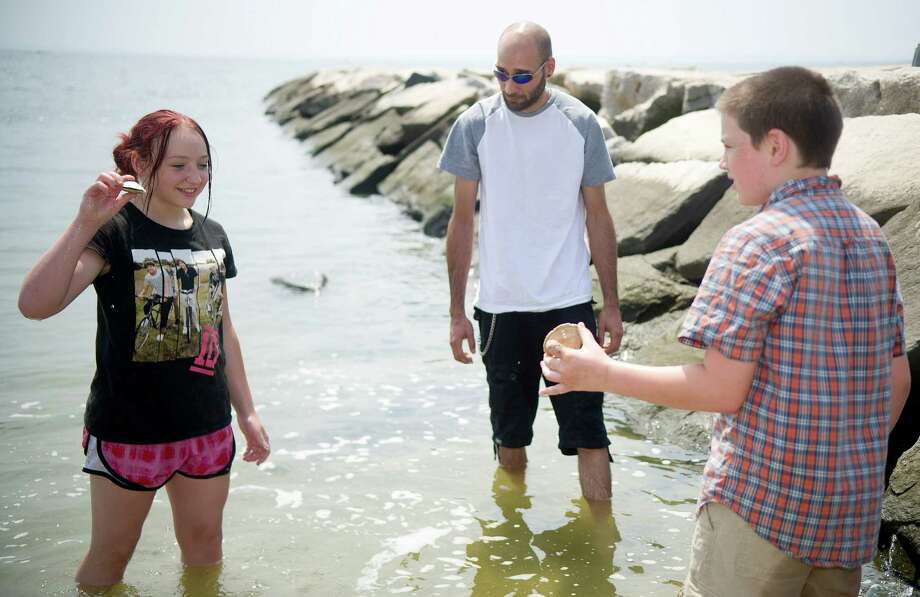 Having moved to Stamford from Ohio just hours before, Malerie Keenan, 13, left, and Joseph Conley, 10, right, stand in the ocean, which they are seeing for the first time, with their mother's boyfriend, Trevor Mancini, center, at Cummings Beach on Saturday, July 20, 2013. Photo: Lindsay Perry / Stamford Advocate