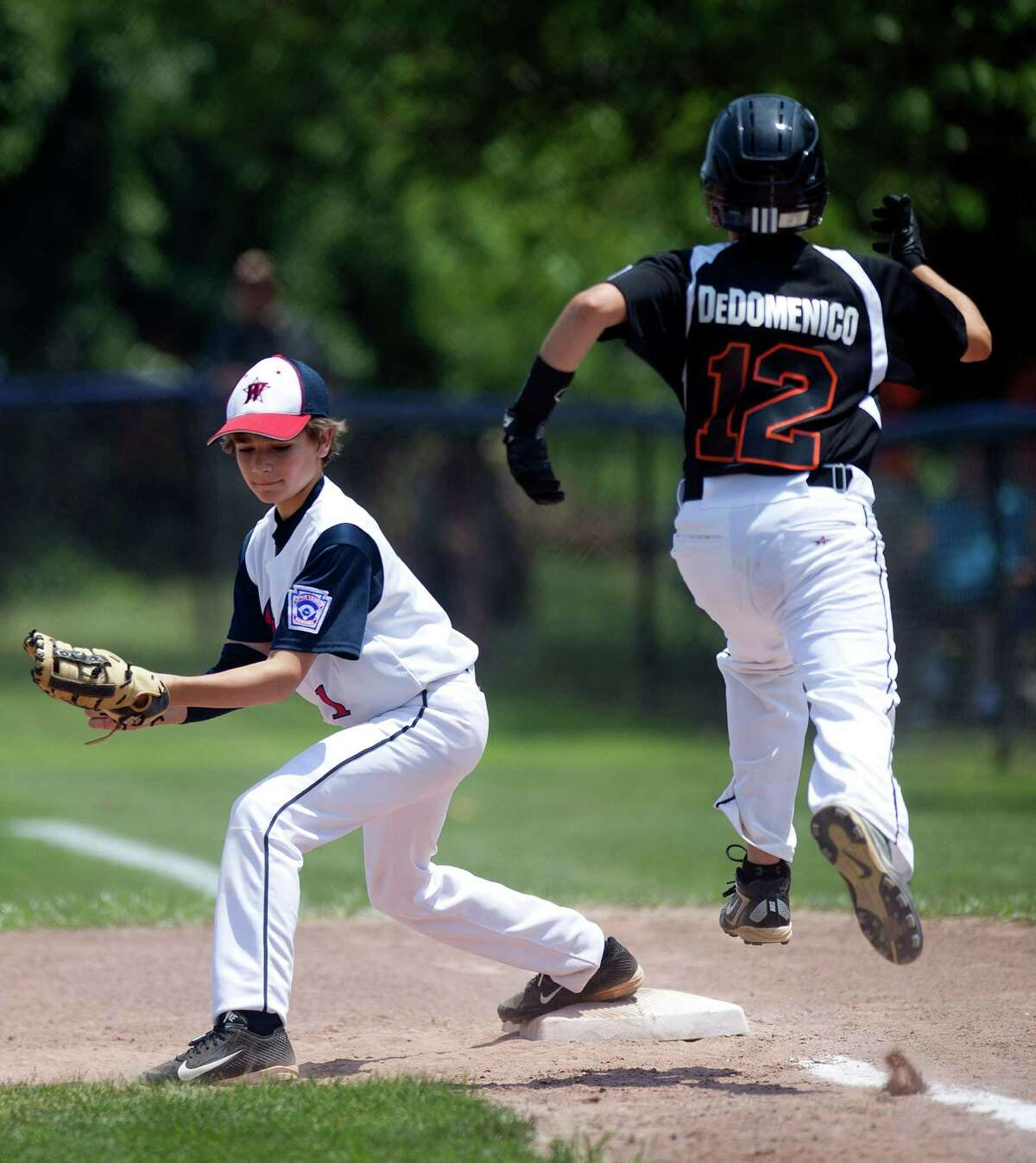 Orange's Drew DeDomenico is out at first as Westport baseman Chris Drbal catches the ball during Saturday's Little League Section 1 tournament game at Frank Noto Field in West Beach Park in Stamford, Conn., on July 20, 2013.