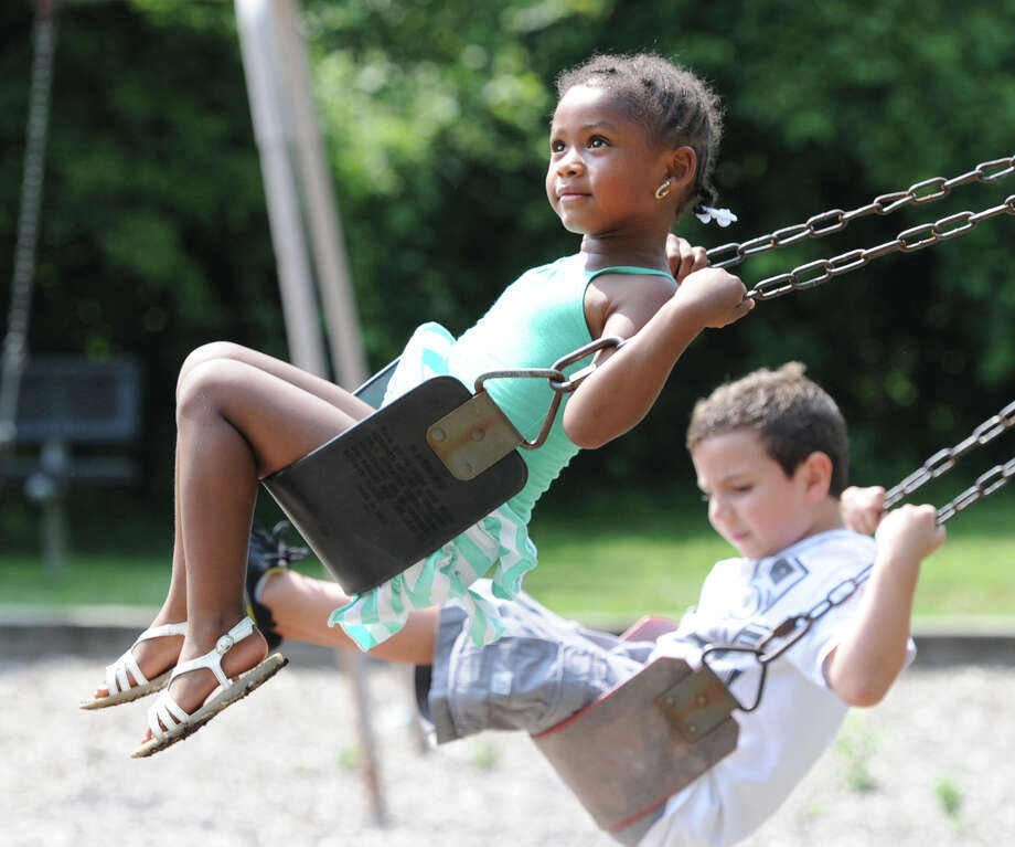 At left, Yaniah Cesario, 5, of Greenwich, gets high in the air while playing on a swing with a friend at the Armstrong Court Housing Complex in the Chickahominy section of Greenwich, Saturday afternoon, July 20, 2013. Photo: Bob Luckey / Greenwich Time