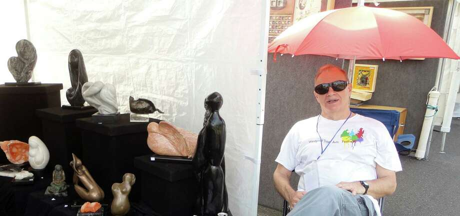 Leeam Aldouby at the booth displaying his wife Sara's stone sculptures while hiding from the sun under an umbrella Saturday during the 40th annual Westport Fine Arts Festival. Photo: Meg Barone / Westport News contributed