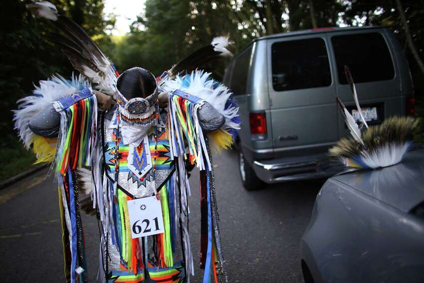 Dennison Brown of Arizona's San Carlos Apache puts on his feathered regalia during the Seafair Indian Days Pow Wow at Daybreak Star in Discovery Park on Friday, July 19, 2013 in Seattle. One year after the event was cancelled because of a lack of funding, the pow wow returned with much fanfare and a grand entry on Friday evening. The event brings Native dancers and drummers from around North America where the dancers compete in their impressive regalia during the event. The pow wow also features Native arts vendors and food booths. You can find more info about the pow wow by clicking here.