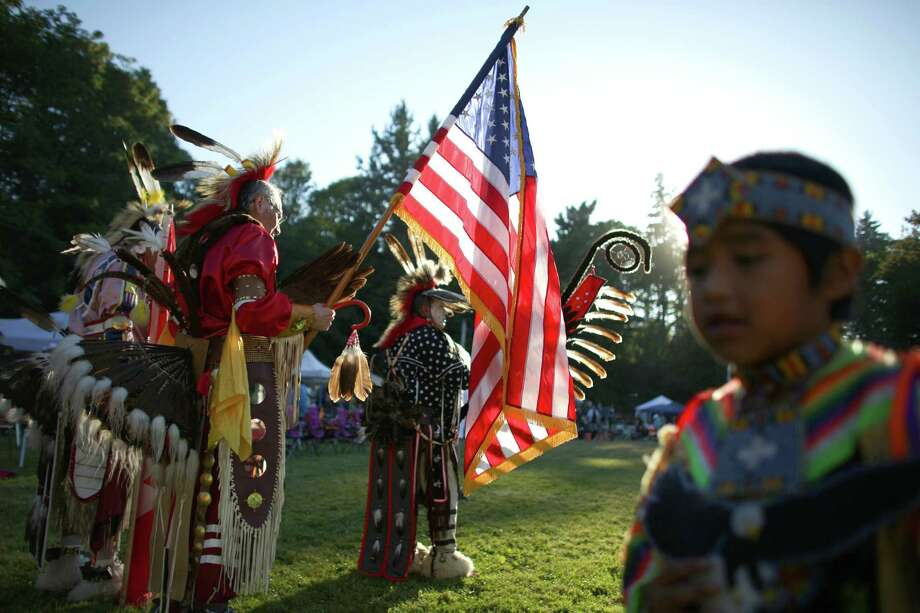 People prepare for the Grand Entry during the Seafair Indian Days Pow Wow at Daybreak Star in Discovery Park on Friday, July 19, 2013 in Seattle. One year after the event was cancelled because of a lack of funding, the pow wow returned with much fanfare and a grand entry on Friday evening. The event brings Native dancers and drummers from around North America where the dancers compete in their impressive regalia during the event. The pow wow also features Native arts vendors and food booths. You can find more info about the pow wow by clicking here. Photo: JOSHUA TRUJILLO, SEATTLEPI.COM / SEATTLEPI.COM
