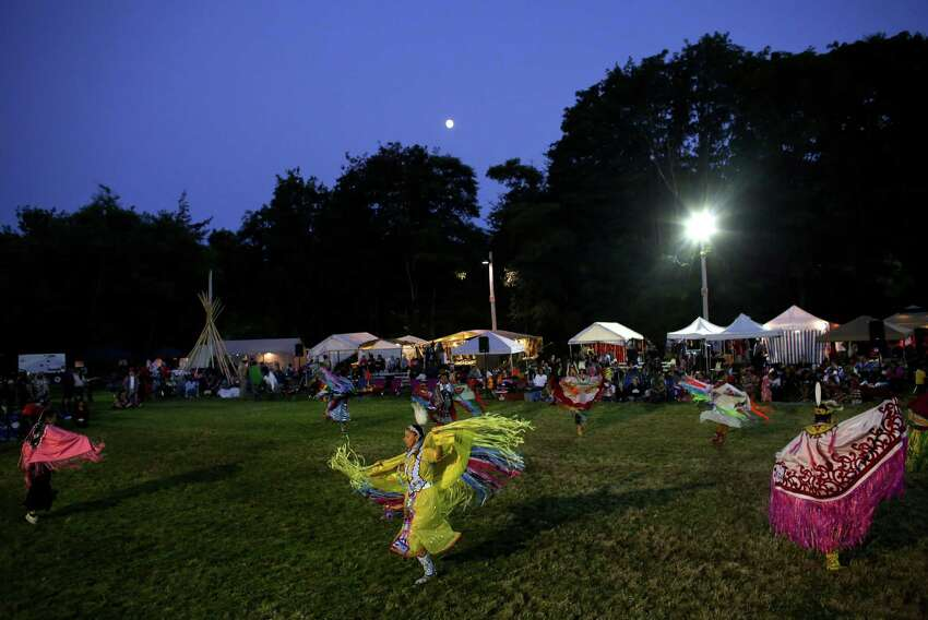 Dancers perform under spotlights and the moon during the Seafair Indian Days Pow Wow at Daybreak Star in Discovery Park on Friday, July 19, 2013 in Seattle. One year after the event was cancelled because of a lack of funding, the pow wow returned with much fanfare and a grand entry on Friday evening. The event brings Native dancers and drummers from around North America where the dancers compete in their impressive regalia during the event. The pow wow also features Native arts vendors and food booths. You can find more info about the pow wow by clicking here.