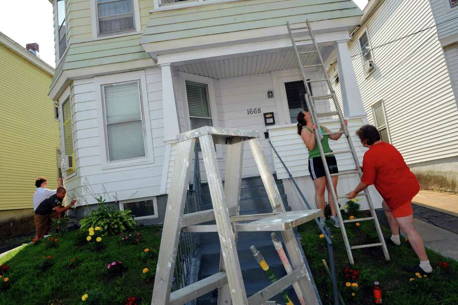 "Volunteers Meredith Becker and Cathy Light, right, assemble a ladder as Kelsey Collins and Kevin Daunais, left, do touch-up painting on the house of Burujit Nandlall during the ""Together We Can Do It!"" a neighborhood revitalization day by the Schenectady Habitat for Humanity on Saturday July 20, 2013 in Schenectady, N.Y. (Michael P. Farrell/Times Union) Photo: Michael P. Farrell / 00023174A"
