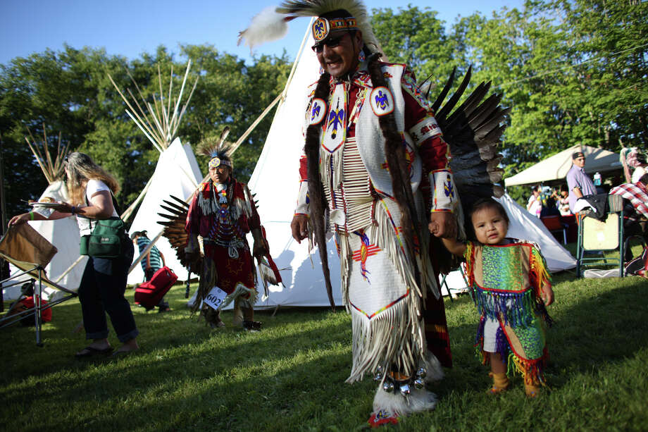 Preston Meanus walks with Dennis, 20 months, during the Seafair Indian Days Pow Wow at Daybreak Star in Discovery Park on Friday, July 19, 2013 in Seattle. One year after the event was cancelled because of a lack of funding, the pow wow returned with much fanfare and a grand entry on Friday evening. The event brings Native dancers and drummers from around North America where the dancers compete in their impressive regalia during the event. The pow wow also features Native arts vendors and food booths. Photo: JOSHUA TRUJILLO, SEATTLEPI.COM / SEATTLEPI.COM