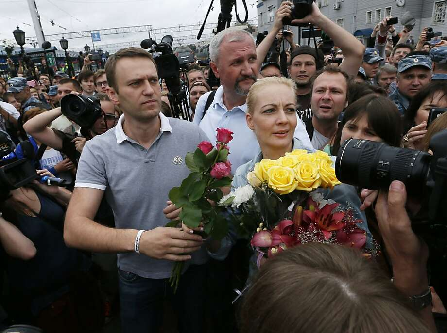 Russian opposition leader Alexei Navalny, left, walks with his wife Yulia after arriving from Kirov at a railway station in Moscow, Russia, Saturday, July 20, 2013. Navalny returned to Moscow on Saturday after his surprise release from jail and vowed he will push forward in his campaign to become mayor of the Russian capital. Navalny was sentenced to five years in prison on an embezzlement conviction on Thursday in the city of Kirov, but prosecutors unexpectedly asked for his release the next morning. (AP Photo/ Dmitry Lovetsky) Photo: Dmitry Lovetsky, Associated Press