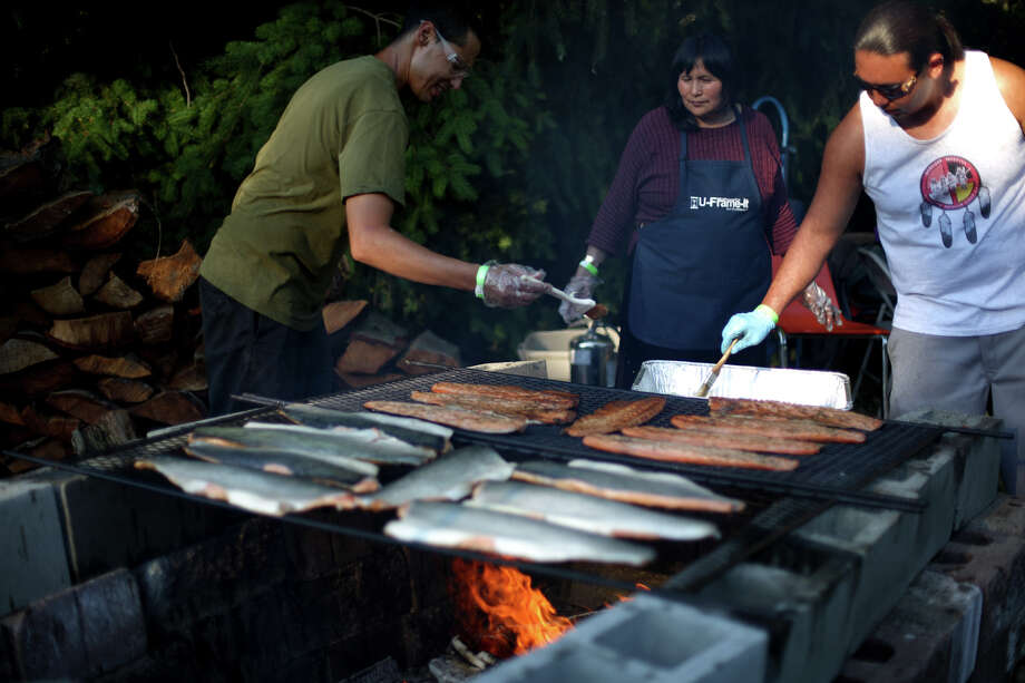 Salmon is grilled during the Seafair Indian Days Pow Wow at Daybreak Star in Discovery Park on Friday, July 19, 2013 in Seattle. One year after the event was cancelled because of a lack of funding, the pow wow returned with much fanfare and a grand entry on Friday evening. The event brings Native dancers and drummers from around North America where the dancers compete in their impressive regalia during the event. The pow wow also features Native arts vendors and food booths. You can find more info about the pow wow by clicking here. Photo: JOSHUA TRUJILLO, SEATTLEPI.COM / SEATTLEPI.COM