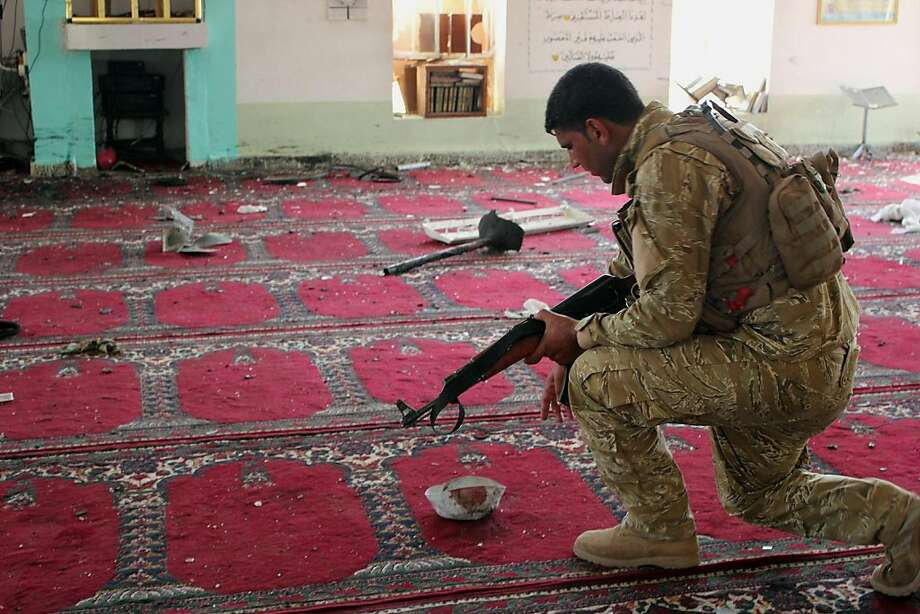 An Iraqi army soldier inspects the damage inside the Abu Bakr Mosque in Baqouba, northeast of Baghdad, Iraq, Friday, July 19, 2013. A bomb hidden in an air conditioner that ripped through a Sunni mosque during midday prayers and other attacks killed dozens in Iraq on Friday, extending a wave of violence targeting worshippers during the holy month of Ramadan.The violence is an extension of a surge of attacks that has roiled Iraq for months, reviving fears of a return to the widespread sectarian bloodshed that pushed the country to the brink of civil war after the 2003 U.S.-led invasion. (AP Photo) Photo: Anonymous, Associated Press