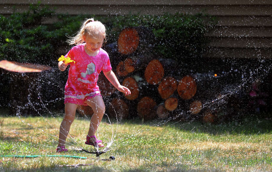 Boston Morrissey, 3, plays by running through a yard sprinkler at her home on Harkness Street in Milford, Conn. on Saturday July 20, 2013 Photo: Christian Abraham / Connecticut Post