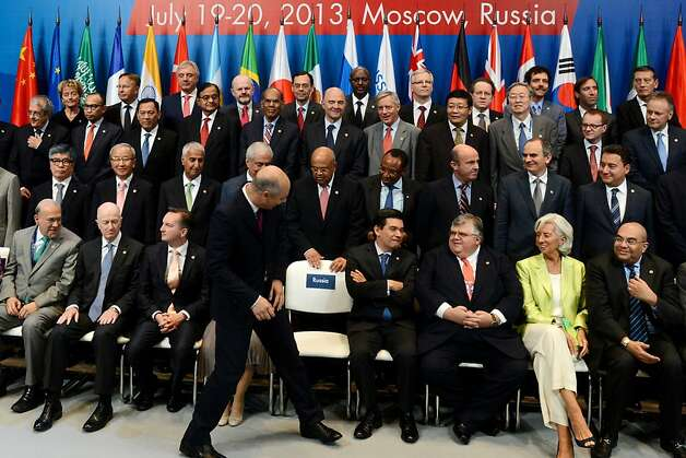 Russian Finance Minister Anton Siluanov takes his seat for the group photo of the world