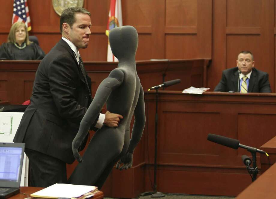 Assistant state attorney John Guy uses a foam dummy to describe the altercation between George Zimmerman and Trayvon Martin to defense witness and law enforcement expert Dennis Root during Zimmerman's trial in Seminole circuit court, in Sanford, Florida, Wednesday, July 10, 2013. Zimmerman is charged with second-degree murder in the fatal shooting of Trayvon Martin, an unarmed teen, in 2012. (Pool photo by Gary W. Green/Orlando Sentinel/MCT) Photo: Gary W. Green, MBR / Orlando Sentinel