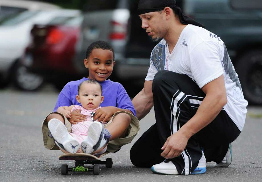 Geams Gill, right, of Danbury, helps Darnell Bronson, 6, and Sparrow Gill, 7 months, ride a skateboard outside of the Glen Apartments in Danbury, Conn. on Saturday, July 20, 2013. Photo: Tyler Sizemore / The News-Times