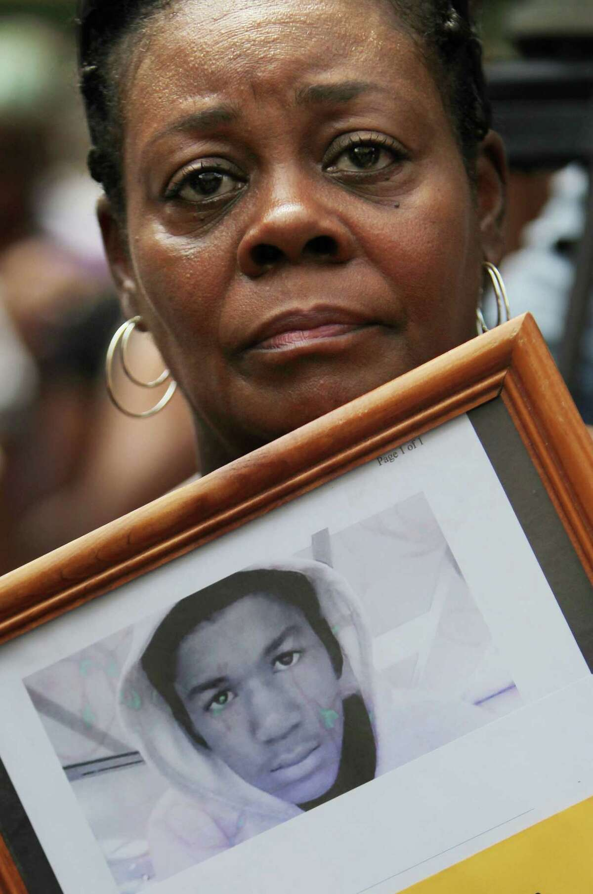 Cheryl Foster holds a framed photo in honor of Trayvon Martin during peace protest at City Hall on Saturday in Houston.