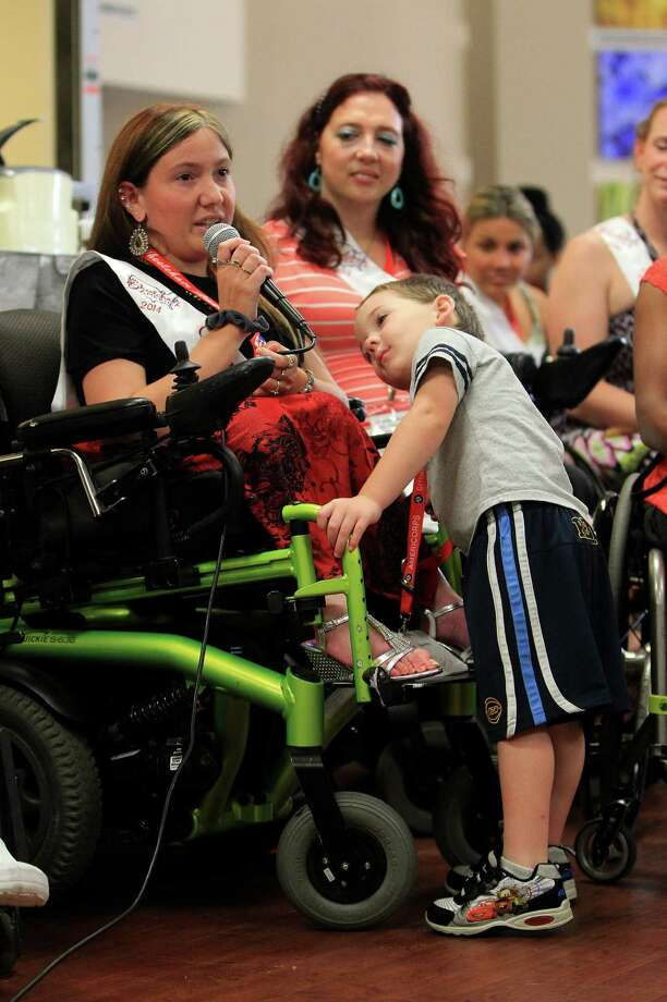 Ms Wheelchair Virginia, Brittany Yates, speaks to the room as her son, Nicholas, 3, watches her as the contestants from the Ms. Wheelchair America 2014 pageant visit The Institute for Rehabilitation and Research at Memorial Hermann Hospital. Photo: Karen Warren, Houston Chronicle / © 2013 Houston Chronicle
