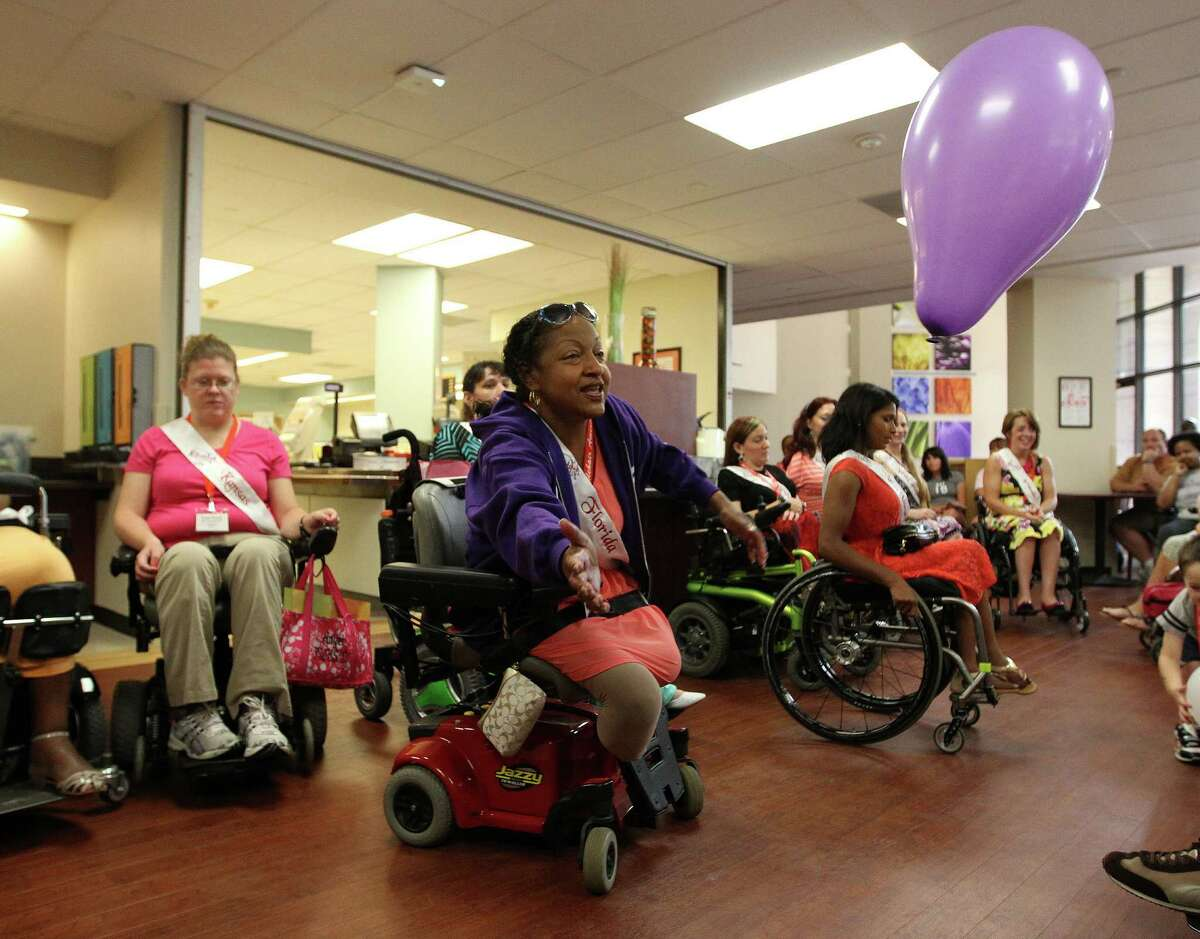 Ms. Wheelchair Florida, Lisa Jackson, plays with a balloon with patients as the contestants from the Ms. Wheelchair America 2014 pageant visited The Institute for Rehabilitation and Research at Memorial Hermann Hospital.