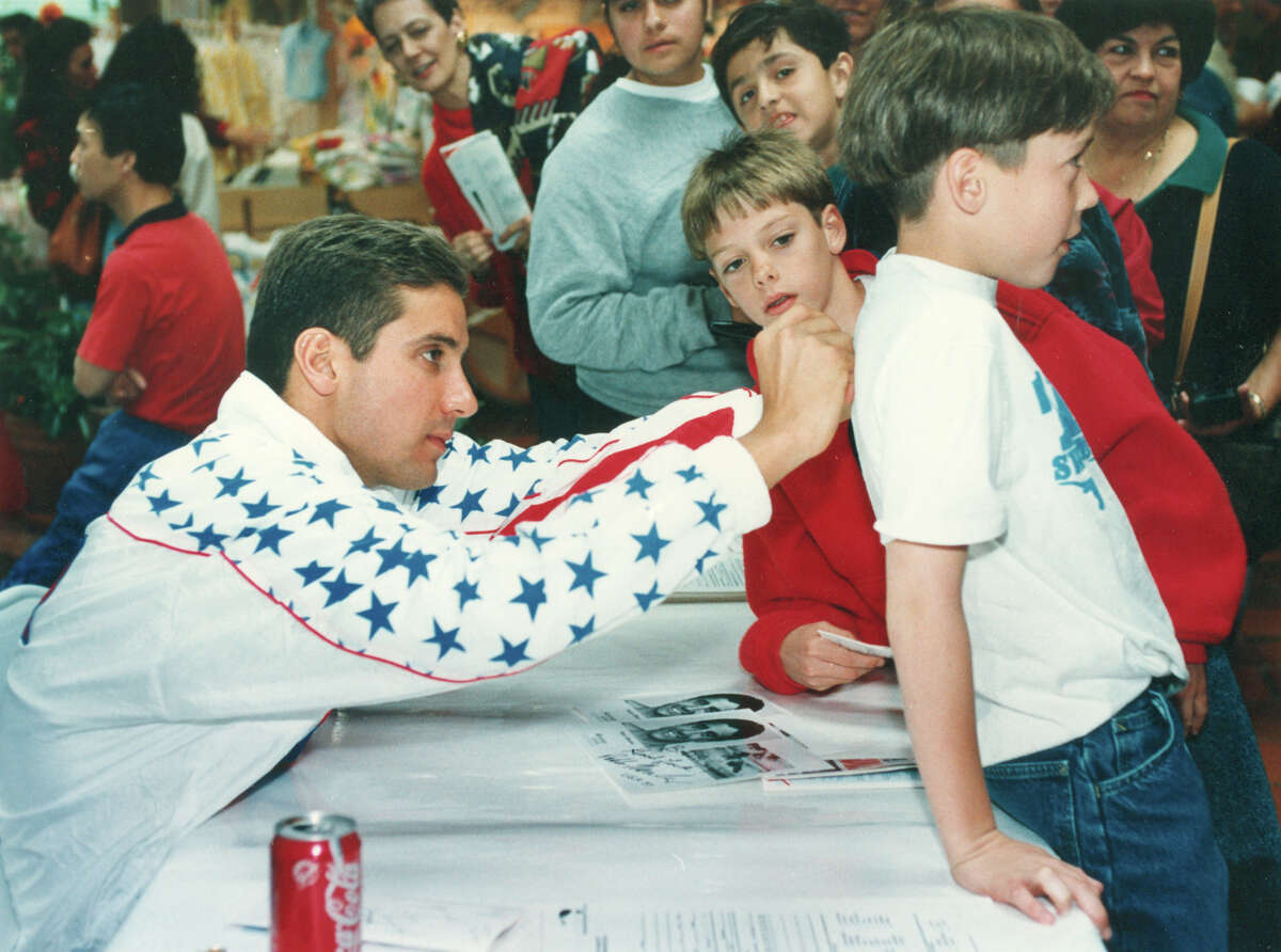Pablo Morales signs the shirt of Roger Gauvreau, 10, a member of a swim team from Brownsville, on Feb. 27, 1993, at North Star Mall. He was there to help promote ticket sales for the upcoming U.S. Olympic Festival.