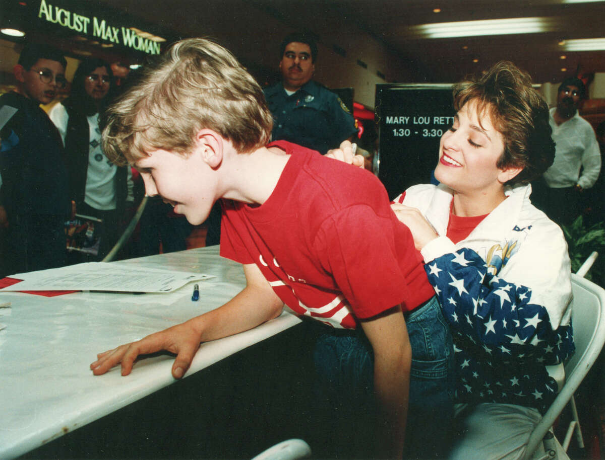 Former Olympic gymnast Mary Lou Retton signs an autograph on the back of 10-year-old Scott Strange's shirt at North Star Mall on Feb. 28, 1993. Retton was on hand to promote ticket sales for the upcoming U.S. Olympic Festival.