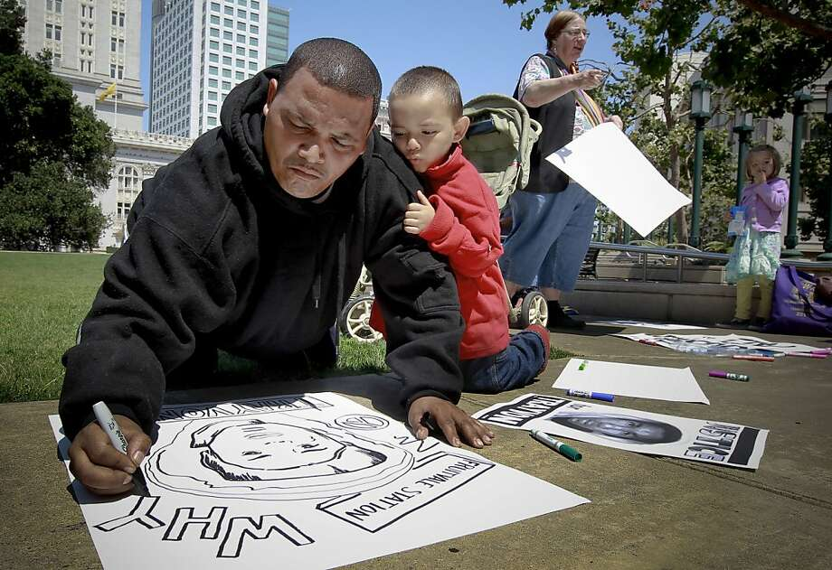 Kumonee Butler and his 3-year-old son Koree, of Oakland design a sign in front of City Hall, preparing for rally demanding justice for Trayvon Martin in front of the Ronald Dellums Federal Building in downtown Oakland, Calif on Saturday July 20, 2013. The crowd joins a nationwide day of protests against last week's acquittal of George Zimmerman in the murder of 17-year-old Trayvon Martin. Photo: Michael Macor, San Francisco Chronicle