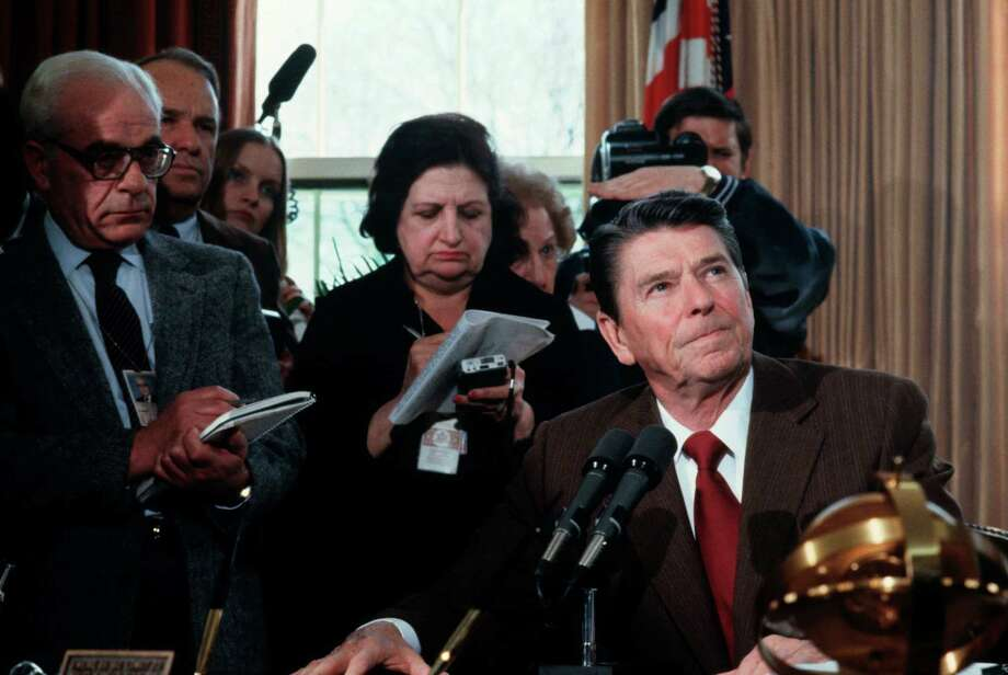 President Ronald Reagan greets the press, including Helen Thomas (C), in the Oval Office during a press conference in the White House in Washington, DC. Photo: David Hume Kennerly, Getty Images / David Hume Kennerly