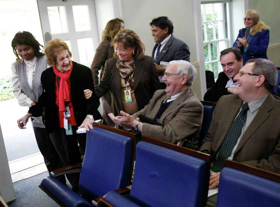 In this Nov. 12, 2008 file photo veteran White House correspondent Helen Thomas is helped to her front row seat in the White House Brady Press Briefing Room in Washington, as she returns after a recent illness. Thomas, a pioneer for women in journalism and an irrepressible White House correspondent, has died. She was 92. She made her name as a bulldog for United Press International in the great wire-service rivalries of old. Thomas used her seat in the front row of history to grill nine presidents _ often to their discomfort and was not shy about sharing her opinions. Photo: Gerald Herbert, Associated Press / AP