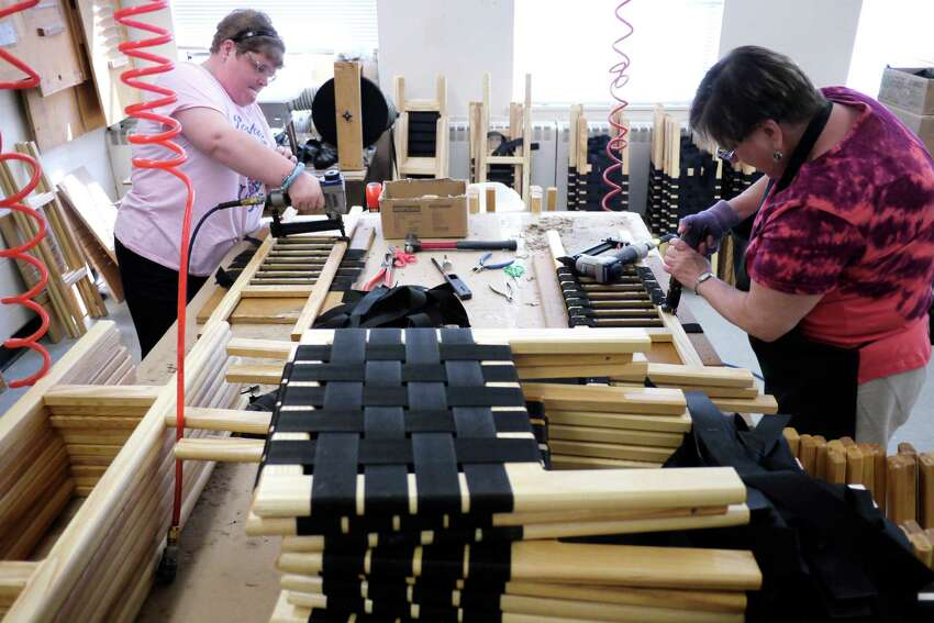 Tonya Norton, left, from Port Henry and VJ Trombley, from Ticonderoga, work on attaching webbing to canoe seats at Essex Industries on Tuesday, July 16, 2013 in Mineville, NY. The workshop employs developmentally disabled people. (Paul Buckowski / Times Union)