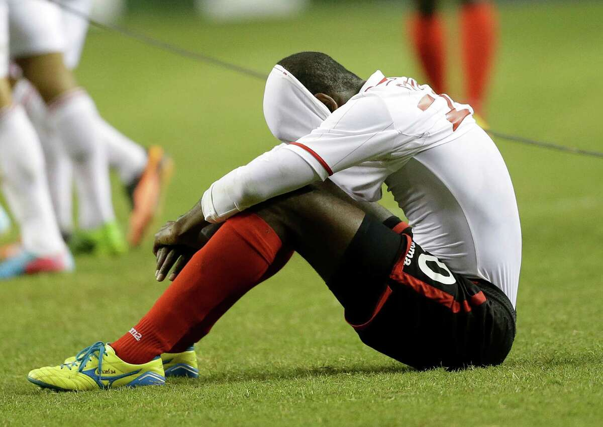 Trinidad and Tobago's Seon Power sits on the turf after the quarterfinals of the CONCACAF Gold Cup soccer tournament against Mexico, Saturday, July 20, 2013, in Atlanta. Mexico won 1-0. (AP Photo/John Bazemore)