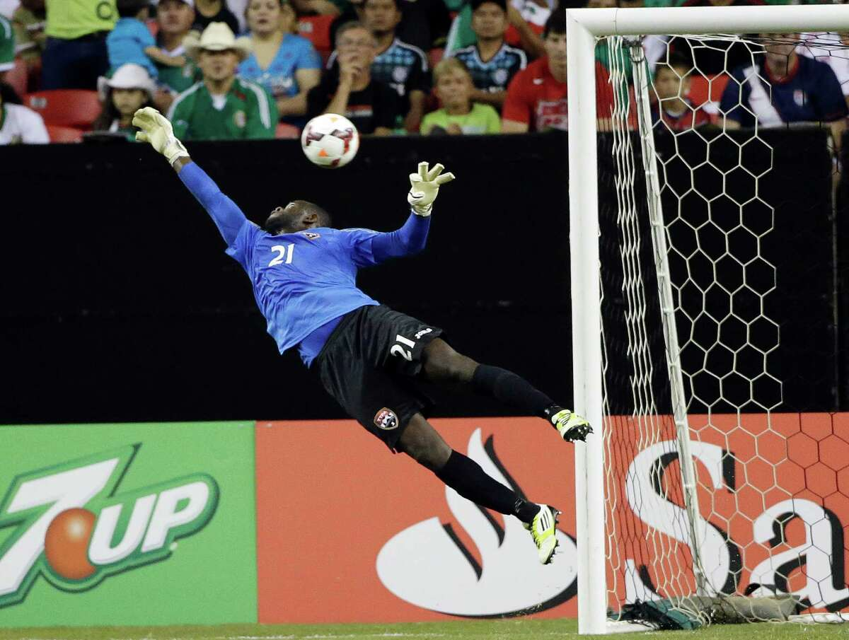 Trinidad & Tobago goalkeeper Jan Michael Williams makes a diving save during the first half in the quarterfinals of the CONCACAF Gold Cup soccer tournament against Mexico, Saturday, July 20, 2013, in Atlanta. (AP Photo/John Bazemore)