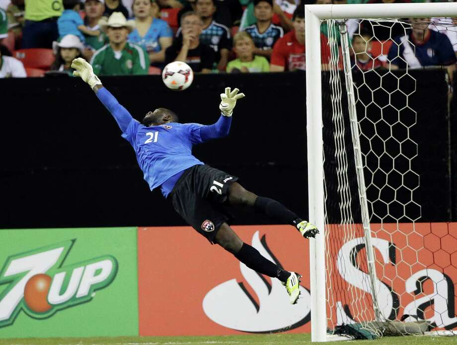 Trinidad & Tobago goalkeeper Jan Michael Williams makes a diving save during the first half in the quarterfinals of the CONCACAF Gold Cup soccer tournament against Mexico, Saturday, July 20, 2013, in Atlanta. (AP Photo/John Bazemore) Photo: John Bazemore, Associated Press / AP