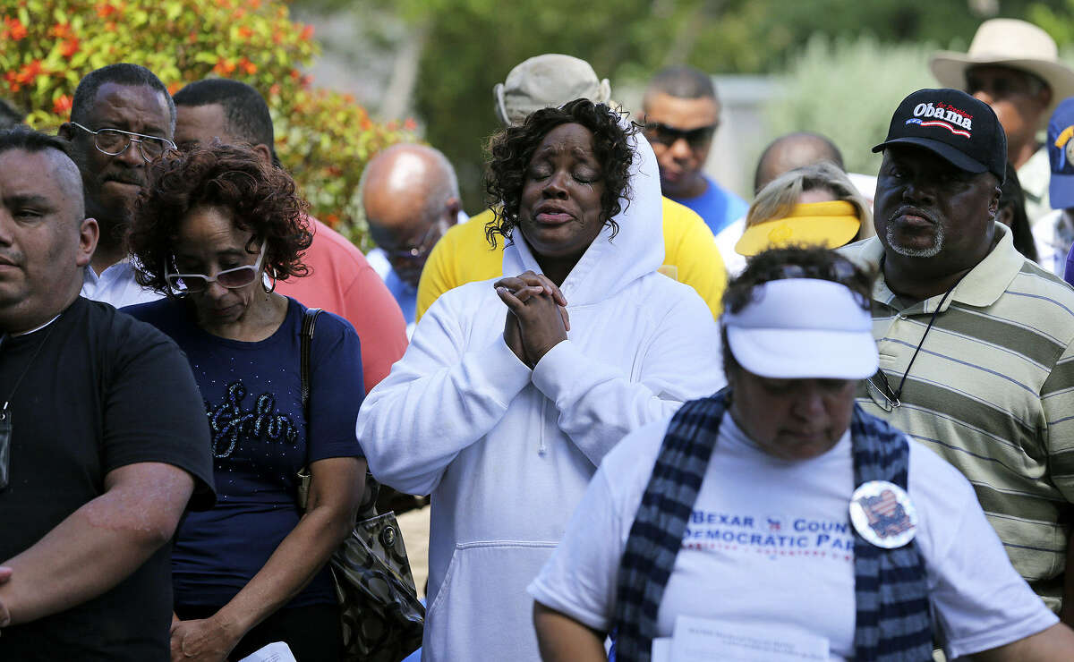 Denise Moten-Harrell (center) joins in prayers during the rally. Religious leaders, politicians and community leaders spoke abut the need to curb violence, rewrite gun laws and educate youths.