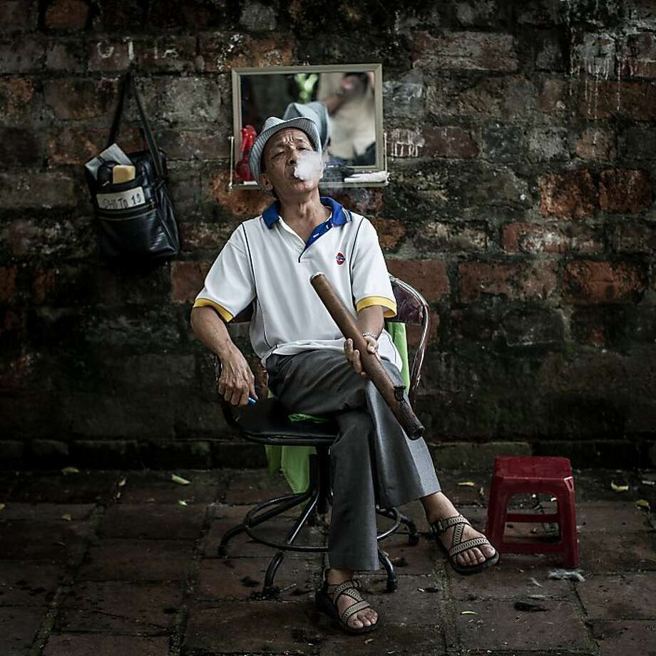 HANOI, VIETNAM - JULY 20: 78 year old street barber Mr Thuan, smokes a pipe as he waits for customers at his roadside barber shop on July 20, 2013 in Hanoi, Vietnam. Mr Thaun has been a street barber for over 30 years after serving in the Vietnamese military. Hanoi's street barbers are a tradition that stretches back to the 18th century. On average a haircut will cost between 1 and 4 USD depending on the fame of the barber and if you are a regular or not. Many of the barbers are ex-miltary personel, retired from service and looking to keep busy or to help cover weekly expenses for their families. (Photo by Chris McGrath/Getty Images) Photo: Chris McGrath, Getty Images
