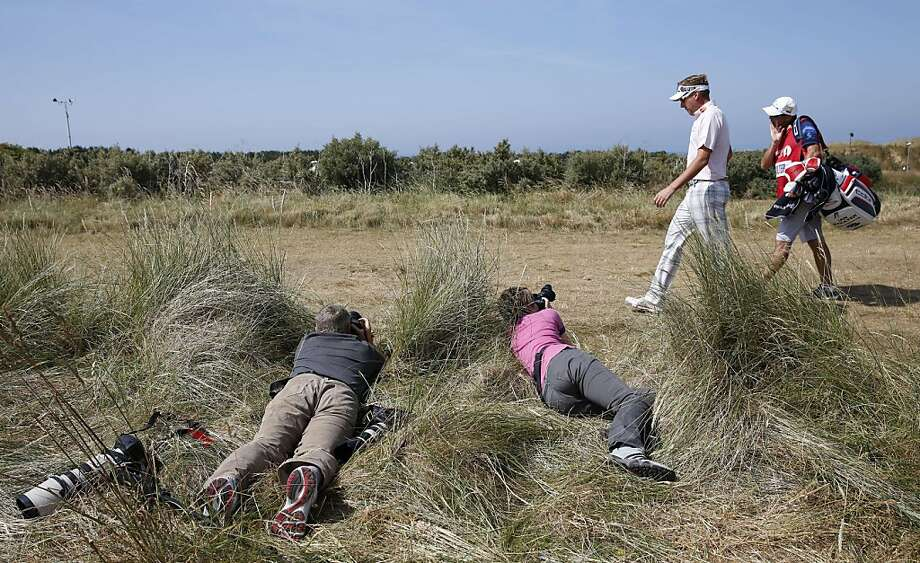 Photographers take pictures of England's Ian Poulter as he walks across a fairway during the third round of the 2013 British Open Golf Championship at Muirfield golf course at Gullane in Scotland on July 20, 2013. AFP PHOTO/ADRIAN DENNISADRIAN DENNIS/AFP/Getty Images Photo: Adrian Dennis, AFP/Getty Images