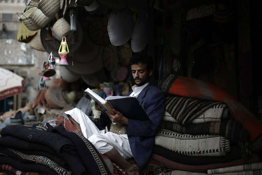 A Yemeni clothes vendor reads verses from the Quran as he waits for customers during the fasting month of Ramadan in the old city of  Sanaa, Yemen, Saturday, July 20, 2013. Ramadan is the holiest month in Islam and observant Muslims worldwide fast from dawn to dusk. (AP Photo/Hani Mohammed) Photo: Hani Mohammed, Associated Press