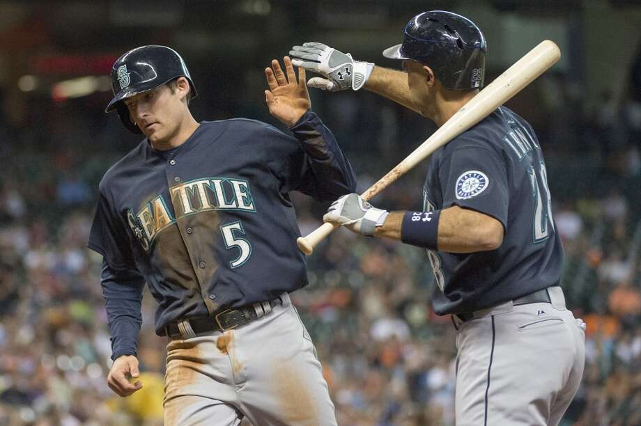 Mariners shortstop Brad Miller (5) celebrates with Raul Ibanez as he scores on a passed ball during the sixth inning.