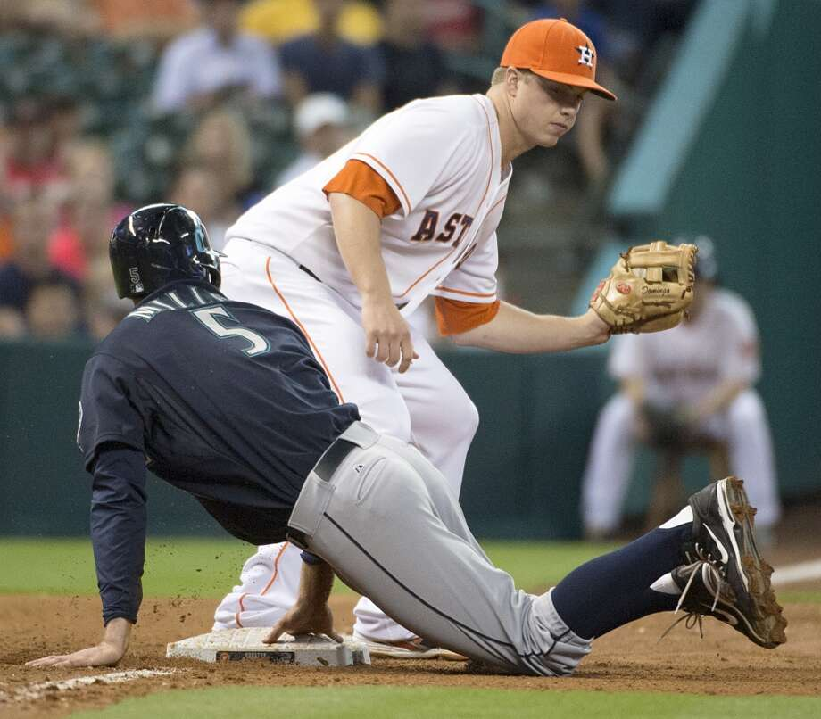 Mariners shortstop Brad Miller is safe at third base as Astros third baseman Matt Dominguez takes the throw during the sixth inning.