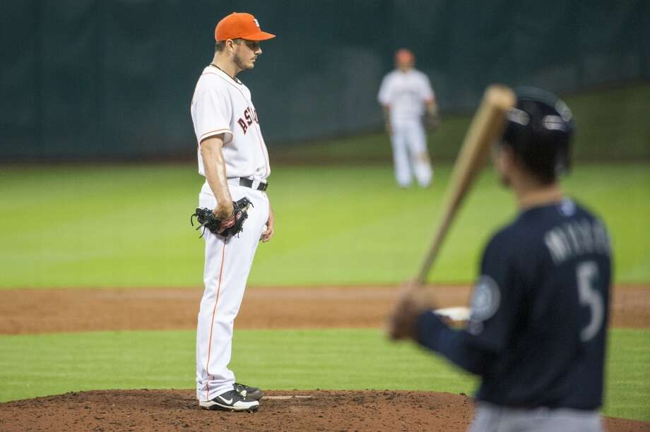 Astros starting pitcher Erik Bedard pauses before facing Mariners shortstop Brad Miller during the sixth inning.