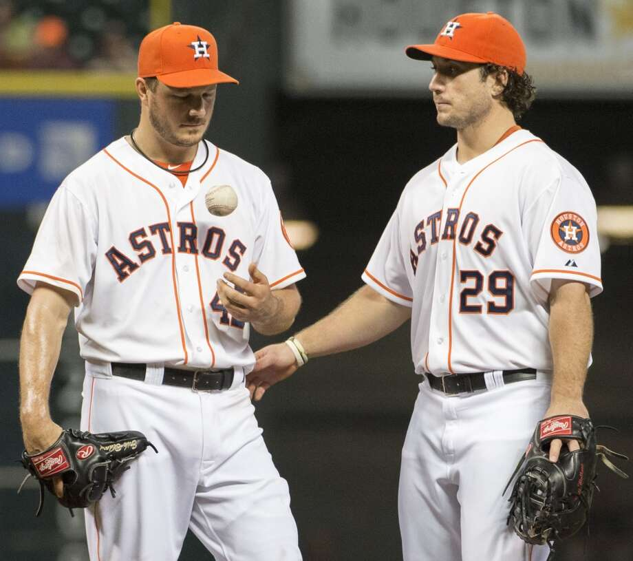 Astros starting pitcher Erik Bedard gets a pat on the back from Brett Wallace as he leaves the game during the seventh inning.