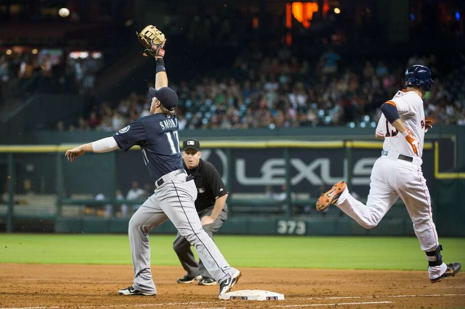 Astros catcher Jason Castro (15) beats the throw to Mariners first baseman Justin Smoak for an infield hit to score Jake Elmore during the fifth inning.