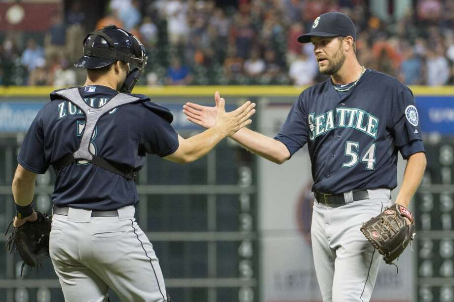 Mariners closer Tom Wilhelmsen (54) celebrates with catcher Mike Zunino after the final out of a 4-2 win over the Astros.
