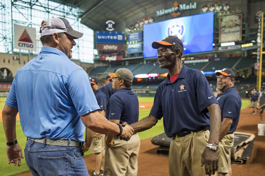 Roger Clemens, left, greets Astros groundskeeper Willie Berry as he visits the stadium before a game against the Seattle Mariners.